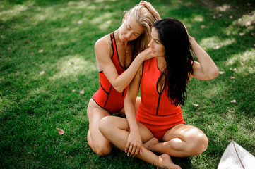 Two attractive girls sitting on the green grass in swimsuits