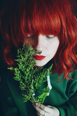 Young red haired woman holding fir twigs