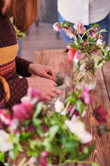 hands of florist collect wedding bouquet at work