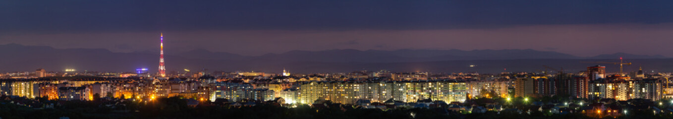 Wide panorama, aerial night view of modern tourist Ivano-Frankivsk city, Ukraine. Scene of bright lights of tall buildings, high television tower and green suburbs on Carpathian mountains background.