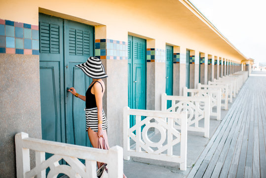 Beautiful woman near the old locker rooms on the beach in Deauville, famous french resort in Normandy