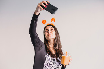 young beautiful woman drinking orange juice and taking a selfie with mobile phone. Wearing a black and white skeleton costume. Halloween concept. Indoors