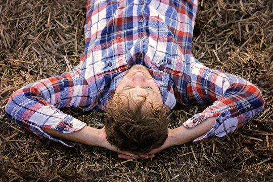 Young Man in Flannel Shirt Relaxing on Hay Bale on Autumn Day