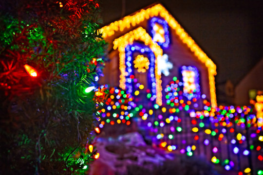 Spruce branches with Christmas ornaments on the background of a house with Christmas lights. Christmas decorations on the facade of the house. Blurred background