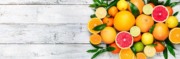 Fresh citrus fruits background. Orange, grapefruit, lemon, lime, tangerine. Mix citrus fruits with leaves. Long web format. Copy space Fototapete