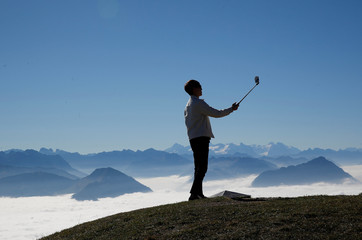A man takes a picture with his smartphone mounted on a selfie stick during sunny autumn weather near the peak of Mount Rigi
