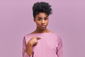 Puzzled dark skinned woman look in bewilderment and frustration at camera, being shocked to be chosen, indicate at themselves. Surprised young African American female gesture indoor