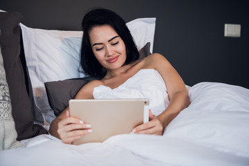A smiling woman lies on the bed scrolling through her tablet.