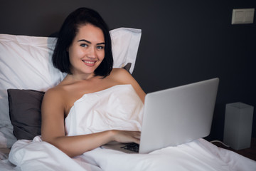 Beautiful woman lying in bed and making a phone call. Young girl using her laptop at home. Beautiful woman relaxing at home.