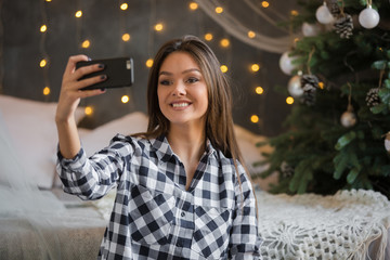 Beautiful girl makes selfie on the background of New Year's scenery