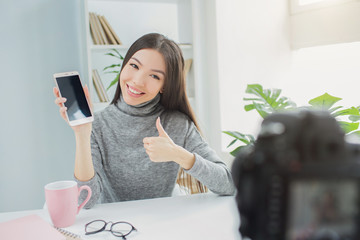 Happy and cool blogger is showing the phone to the vlogging camera. She likes her new present. Young woman is showing the big thumb up. She can recommend this phone to her subcribers.