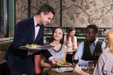 Smiling waiter serving visitors of restaurant