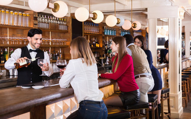 Portrait of barman and people who are standing near bar counter in luxurious restaurant