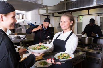 Waitress taking cooked meals from chef