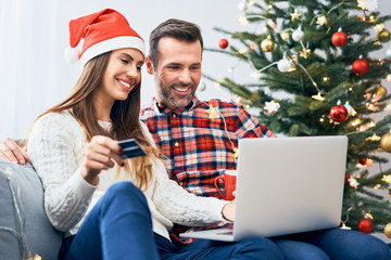 Couple sitting on sofa and doing christmas shopping online with credit card and laptop