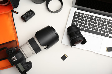 Laptop and professional photographer's equipment on table, top view
