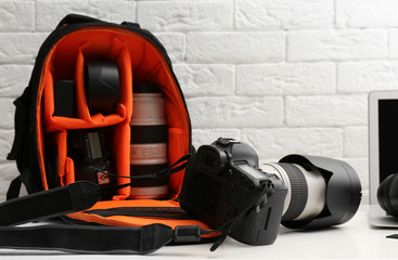 Camera and backpack with professional photographer's equipment on table indoors
