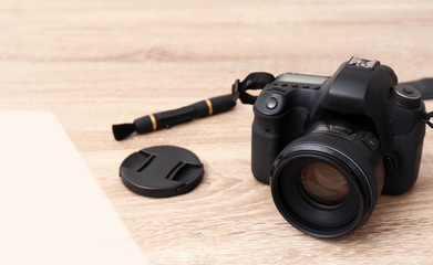 Professional camera and space for text on wooden table. Photographer's equipment