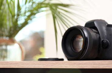Professional camera on table against blurred background, space for text. Photographer's equipment