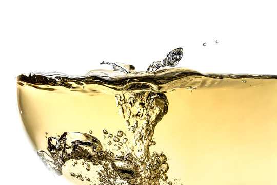 Splash white wine in glass with bubbles close-up macro texture isolated on top on white background. Wave of white wine with beautiful fizz.