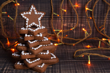 Traditional Christmas gingerbread cookies are folded in the shape of a Christmas tree, on old boards and luminous garland, minimal idea, copy space