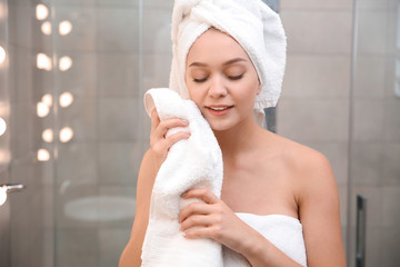 Beautiful woman with clean towels in bathroom