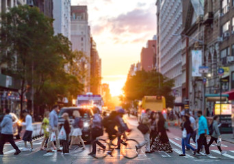 Fotomurales - Crowds of people cross a busy intersection on 23rd Street and 6th Avenue in Manhattan with the colorful sunset in the background skyline