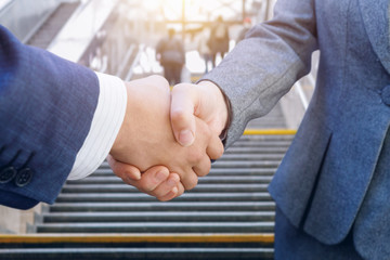 A handshake of a businessman and a businesswoman at the city stairs going up background.