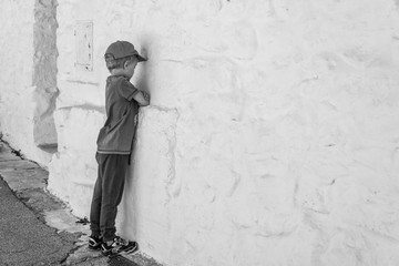 Huffed boy stay in front of the white wall.