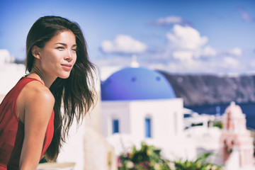 Wall Mural - Luxury Europe cruise travel vacation Santorini woman looking at view. Tourist Asian girl relaxing at three blue domes, Oia, Greece, european destination.