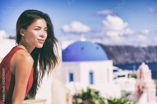 Wall mural Luxury Europe cruise travel vacation Santorini woman looking at view. Tourist Asian girl relaxing at three blue domes, Oia, Greece, european destination.