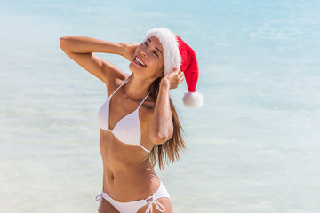 Wall Mural - Happy santa hat chinese tourist woman playful on Caribbean beach tropical getaway. Luxury travel vacation for Christmas holidays. Asian model in bikini.