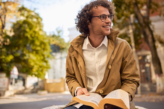 Happy young man with glasses reading and posing with book outdoors. College male student carrying books in campus in autumn street. Smiling guy wears spectacles and curly hair reading books outside