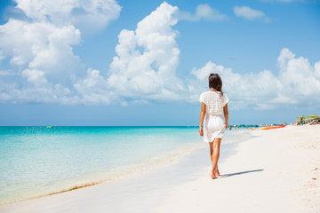 Caribbean beach luxury vacation summer holiday woman walking on perfect white sand tourist destination.