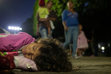 A girl, part of a caravan of thousands of migrants from Central America en route to the United States, sleeps in Tapachula, Mexico
