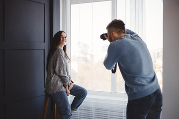 Photographer taking pictures of female model in studio. Natural light photo shoot. Professional photography job