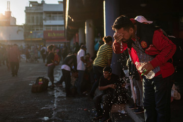 A migrant, part of a caravan of thousands of migrants from Central America en route to the United States, uses a bottle of water to wash himself in the Tapachula city center