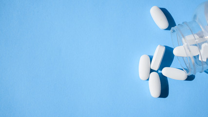 Oxycodone pills. Opioid pain medication, narcotic. Close up white pills with a bottle on a blue background