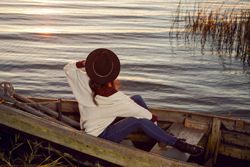 woman in a red plaid shirt sits in a wooden rowing