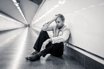Sad young businessman jobless suffering from depression sitting depressed on ground street subway