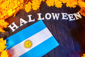 Argentine flag and the inscription Halloween. Halloween in Argentina. Flag of  Argentina surrounded with yellow oak leaves.