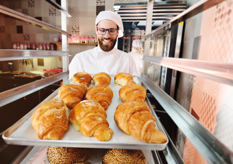 A young handsome male baker holds a tray with French croissants in front of a bakery and smiles.