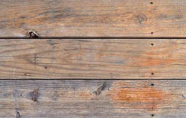 The surface of an old pressure treated picnic table showing wear from weather.