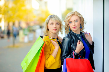 two beautiful happy girls with shopping bags near the shop window
