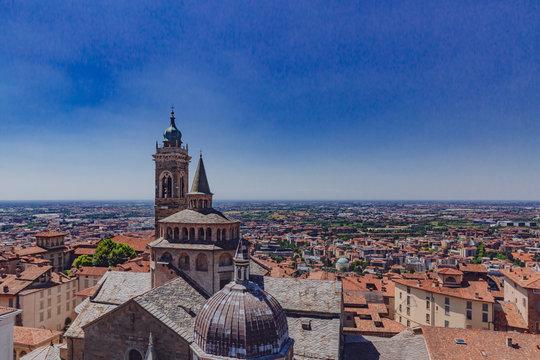 View of Basilica of Santa Maria Maggiore and the lower city of Bergamo, Italy under blue sky