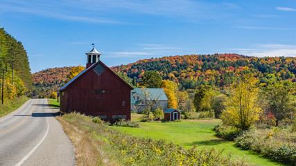 red barn along a country rural road  with woods dressed in bright autumn colors of fall foliage