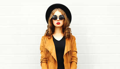 Fashion woman in black round hat, sunglasses, jacket on gray wall background