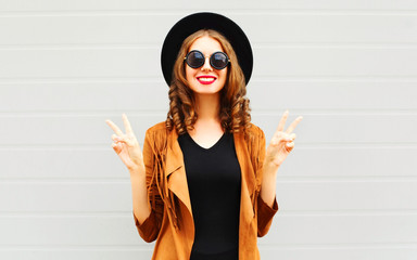 Fashion cool smiling girl in black round hat, sunglasses and jacket on gray wall background