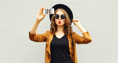 Fashion woman taking picture selfie by smartphone in black round hat, sunglasses, brown jacket on gray wall background