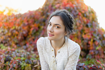 Beautiful girl in a white lace blouse in an autumn park
